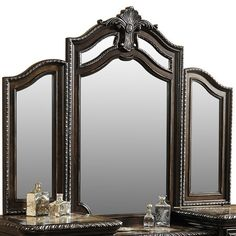 Bring elegant style to your master suite with this dark brown vanity mirror, showcasing an embellished arched top and scrolling trim.  ...