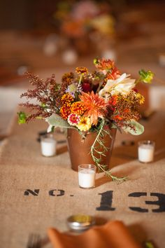 Autumn tablescape with burlap runner and floral centerpieces in copper vessels