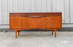 Exceptional bowed front mid century modern credenza / sideboard in magohany and palisander.
