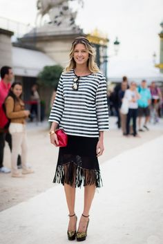 Helena Bordon wears a striped top with a fringe skirt and metallic platforms.