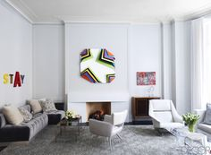 In the living room of a Manhattan townhouse renovated by Timothy Haynes and Kevin Roberts of the firm Haynes-Roberts, a custom-made sofa upholstered in a Larsen silk velvet and a 1960s Italian armchair covered in a Ralph Lauren Home fabric flank 1960s cocktail tables by Paul McCobb; the leather armchair by Carlo di Carli and console by Batistin Spade are from the 1950s; the artworks are by Jack Pierson, Jim Lambie, and Gerhard Richter.