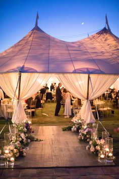 A walkway of candle light and flowers lead the guests into the entrance of the dinner reception held inside the zephyr tent on the Croquet Lawn at Rancho Valencia Resort. Wedding Coordination by Thomas Bui Lifestyle Flower Design by Adorations Botanical Artistry