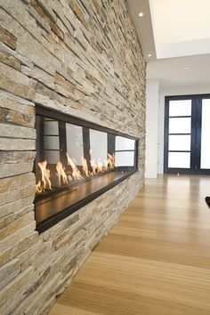 Pretty long fireplace on natural stone wall. Love raised fireplaces! (the floors are nice too.)