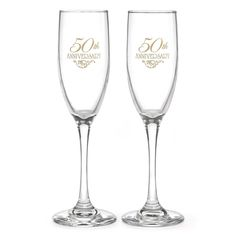 "Flourish 50th Wedding Anniversary Toasting Flute Set includes two toasting flutes. They feature a classic flute design and shape with a thick and sturdy base, a thin stem, and a glass bowl on top in a traditional flute shape. The front of each flute is printed in gold with the phrase ""50th Anniversary"" and an elegant flourish accent. The back of each flute can be personalized."