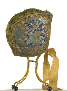 Gorro (child's round cap), 1730. In two-tone green brocade with gold thread and silk floral polychrome draw. Trimmed with Spanish lace. There are wo straps to hold it under the chin, in yellow silk taffeta.Lined with linen weave in color.  This type of child cap fits close to the head and was used by children in the eighteenth century in early childhood. Both the fabrics and decorative motifs are the same as those used in the dresses. (c) Museo del Traje
