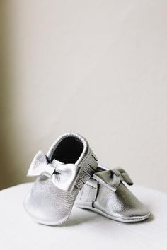 Our handmade SILVER BOW baby moccasins are 100% leather, and are oh so sweet for baby's tiny little toes! These moccasins are gender neutral.  S I Z I N G   G U I D E Size 1: fits infants aged 0-3 months. Size 2: fits infants aged 3-6 months. Size 3: infants aged 6-12 months.