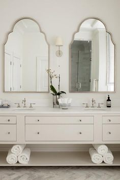silver Bathroom Decor To silver arch mirrors flank a nickel sconce mounted over an ivory double washstand boasting a shelf, glass knobs, and satin hook and spout faucets fixed to a honed white marble countertop. Modern Bathroom Tile, Silver Bathroom, Classic Bathroom, Bathroom Interior Design, Small Bathroom, Bathroom Ideas, Bathroom Designs, Mirrors Silver, White Bathroom Mirror