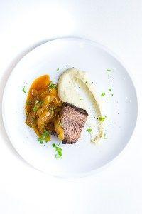 Leckeres Gericht aus dem Smoker: Geräucherte Rinderbrust (Beef Brisket) mit Bohnenpüree und Bierzwiebeln.