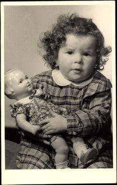 Foto Ak Kleinkind mit einer Puppe in Händen, Sitzportrait