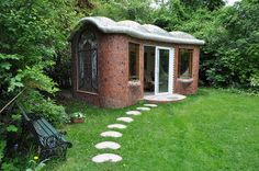 Small get-away-home built for about £5,000. || Cement, curved wood, chicken wire, concrete, broken tile, and mosaic stained-glass windows.