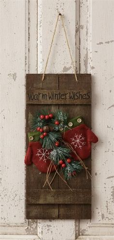 """Warm winter wishes"" sign adorned with mittens, berries and greenery."