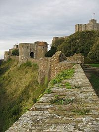 """Dover Castle is a medieval castle in the town of the same name in the English county of Kent. It was founded in the 12th century and has been described as the """"key to England"""" due to its defensive significance throughout history.It is the largest castle in England."""