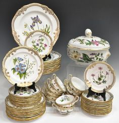 """Spode 'Stafford Flowers' Bone China dinner service, Y8519, each having parcel gilt rim and an assortment flowers, comprising: (12) dinner plates in the 'Iris and Sphaerolobium' pattern, 11""""diam; (12) salad plates in the 'Lida and Acacia' pattern, 7.75""""diam; (11) bread plates in the 'Tachiadenus' pattern, 6""""diam; (12) tea cups in the 'Camellia, Polygala, and Thunberia' pattern, 2.25""""h, 3.75""""diam; (12) saucers in the 'Oxalis' pattern, 6""""diam; (1) lidded tureen in the 'Nepeta, Paeonia,"""