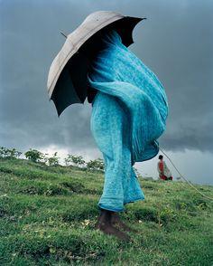 LA FEMME EN BLEU © Laurent Weyl - Au Sud-Ouest du Bangladesh, dans le district de Satkhira, une vieille femme garde sa vache sur la digue. Avec le réchauffement climatique le régime de la mousson a changé. La mer inonde et tue les cultures. De plus en plus de Bangladais doivent quitter leurs terres. En 2005 le photographe français Laurent Weyl s'est rendu sur place, là où le réchauffement climatique fait le plus de dégâts. - En savoir + : http://www.6mois.fr/La-femme-en-bleu-par-Laurent-Weyl