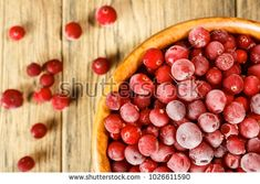 The frozen cranberries in a wooden bowl. Rustic style. The frost on the berries.