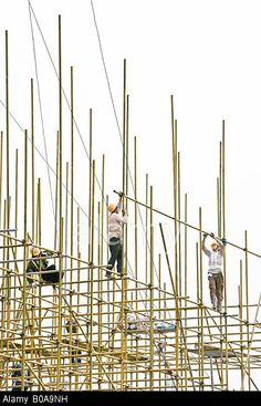 Construction workers on scaffolding, low angle view. © PhotoAlto / Alamy