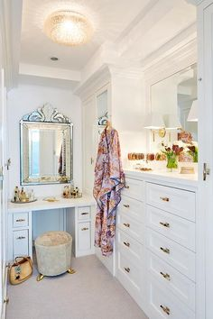 Glam walk-in closet features a round light gray stool on gold feet as well as a white built-in makeup vanity tucked under a Venetian mirror.