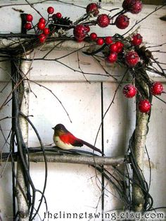 A rustic window frame is constructed of white birch branches, and intertwined with curling twigs. It is adorned with frosted crimson berries and dried pine cones. The star-like blooms of dried ivory German statice arch gracefully like tiny constellations. A faux woodland bird perches for a moment on the window ledge. The frame measures 15 x 15, and the outermost measurement, from splaying branch tip to splaying branch tip is approximately 21 wide x 21 high.  This window arrangement would be…