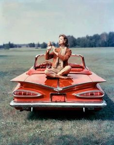 Old Hollywood actress on top of red vintage car thunderbird at drive in