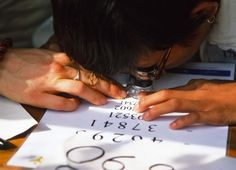 A  Burmese child with extremely poor vision tries to read for the first time with an aid donated by Sight For All