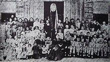 Luíza Morelli Marchioro e seus alunos em frente de sua residência-escola.