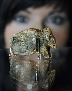 """""""A woman views what is claimed to be the oldest known art work at the Neanderthal Museum in Mettmann, Germany. The ivory carving of a mammoth, 35,000 years old, was found in southern Germany."""""""