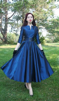 """Lorreta $199.95 The bodice features three-quarter length sleeves and a modified boat neck with a center front slice. Taffeta covered buttons close at the back. The full circle skirt will """"swish"""" as you move. A wide belt with decorative buckle accents the waistline. Colors: Dk Blue, Dk Green, Black, Silver, Dk Red, Plum, Bras or Copper. Acetate Taffeta, please dry clean only."""