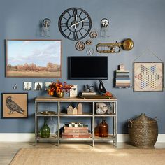 Create the perfect gallery wall using pictures, easy projects, and collectibles or memorabilia. To de-emphasize a TV, place it slightly off-center and balance it with a larger piece of art. Place the TV at eye level to avoid eye and neck strain for seated viewers, but don't be afraid to hang other things below eye level. We kept this color palette earthy and muted with antiques and nature-inspired art.