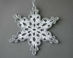 White crochet snowflakes with silver edge. Handmade Christmas ornaments made with high quality cotton thread and silver lame thread in smokefree and petfree environment. Each snowflakes measures 4.7x 4.7 approx. (12 cm x 12 cm) Starched to keep them in shape. For other crocheted items, please visit my shop: https://www.etsy.com/shop/SevisMagicalStitches?ref=l2-shopheader-name For hand knitted items, please visit my other shop: https://www.etsy.com/shop/VistaStudioVS?ref=search_shop_red...