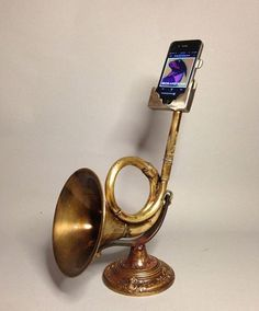 Iphone stand made from an antique car horn, parts from other horns, and a recycled lamp base. The horn amplifies the sound from the Iphone. By Christopher Locke. #ModernArt #IphoneStand