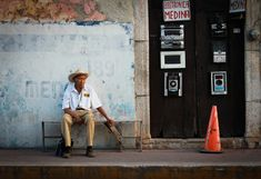 valladolid mexico man sits in front of wall