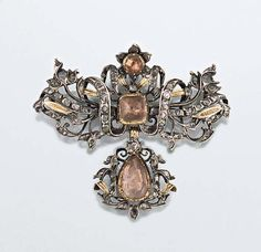 An 18th century topaz and diamond brooch The rose-cut diamond openwork looped ribbon bow surmount centrally set with a square and a circular topaz, with reeded gold leaf accents, suspending a matching pear shaped topaz drop, probably Portuguese, in silver mounts, the topaz with coloured foil backs, later brooch fitting