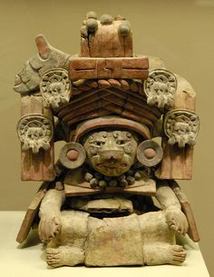 This ceramic urn or vase made by the ancient Zapotecs of Oaxaca shows a seated man in an elaborate headdress wearing an animal mask