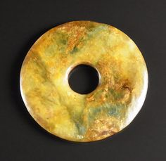 A Chinese jade bi disc. Neolithic period. Of plain, circular form, the stone of a translucent brown, green and yellow tone. 3.7 in (9.3 cm) diameter.