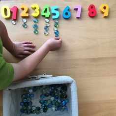 Morning number work with our Hape numbers and glass beads from the dollar store…