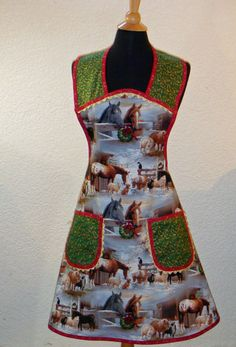 Horses, sheep, cats and dogs in a snow covered barnyard is a serene setting for this non traditional Christmas print apron. A holly print accent fabric mimics the color of the wreaths and red bows hanging in the stable. Gold metallic rick rack peeks out of the top of the bodice and the pockets. Scarlet bias tape encases the apron and is embroidered in Christmas colored leaves.  This lovely apron will fit a M-Xl or a 16-20.