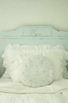 Pretty ruffled pillows against a vintage-style headboard