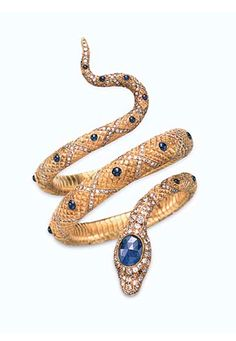 A SAPPHIRE AND DIAMOND SERPENT BRACELET   Designed as a textured gold coiled snake, the body enhanced by cabochon sapphire and single-cut diamond 'X' motifs, with an old European-cut diamond and rose-cut sapphire head and circular-cut ruby eyes, mounted in gold, 2¼ ins. diameter