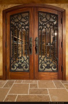 The doors to the wine cellar are mahogany, like the front door, but have iron panels in an intricate design.