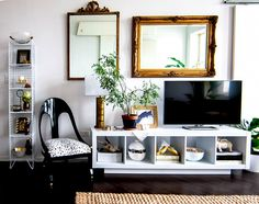 TV Console and Gold Frames on Wall