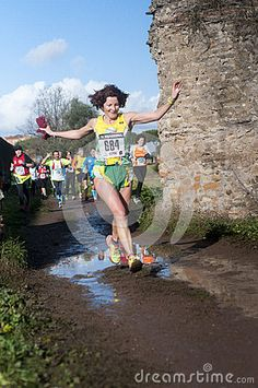 Female competitor at Marathon of the Epiphany, Rome  Female competitor jumping puddle in road during Marathon of the Epiphany in Parco Degliacquedotti, Rome, Italy. Photo taken on: January 06th, 2016