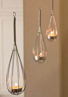Oh why, why, why didn't I think of this sooner? And you can hang things from the bottom of the whisks to be even more decorative! (I would use those little battery tea lights if I were indoors.)