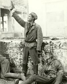 A Red Army Soldier standing next to dead German soldiers while getting ready to shoot a flare, Stalingrad
