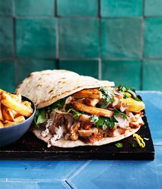 It could be said that this gyro classic is a little over the top, but what's not to love about a sandwich stuffed with roast pork and hot chips? We've made small pita for this recipe, but shop-bought will work fine. Start this recipe a day ahead to dry the pork skin.