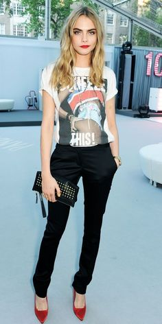 Cara Delevingne in graphic t-shirt, black pants, and what appear to be either red velvet or suede heels.
