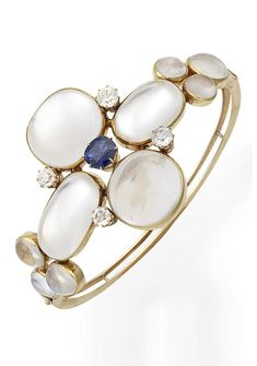An antique moonstone and sapphire bangle, circa 1895. The hinged bangle designed as a quatrefoil of cushion and oval-shaped cabochon moonstones, with a central cushion-shaped sapphire, accented by circular-cut white sapphires, between further trios of cabochon moonstones, mounted in gold.