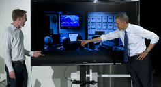 Barack Obama points to a picture of himself looking at a weather map. | Getty