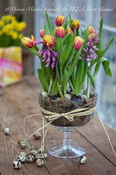 Use spring blooms placed in glass trifle dish, then wrap the glass with burlap and hot glue antique buttons to the burlap.
