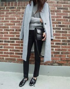 grey and mannish, slung over the shoulders in a nonchalant way