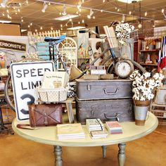 """Have you noticed our new """"travel"""" themed table in the front?! What unique place are you visiting this summer?"""